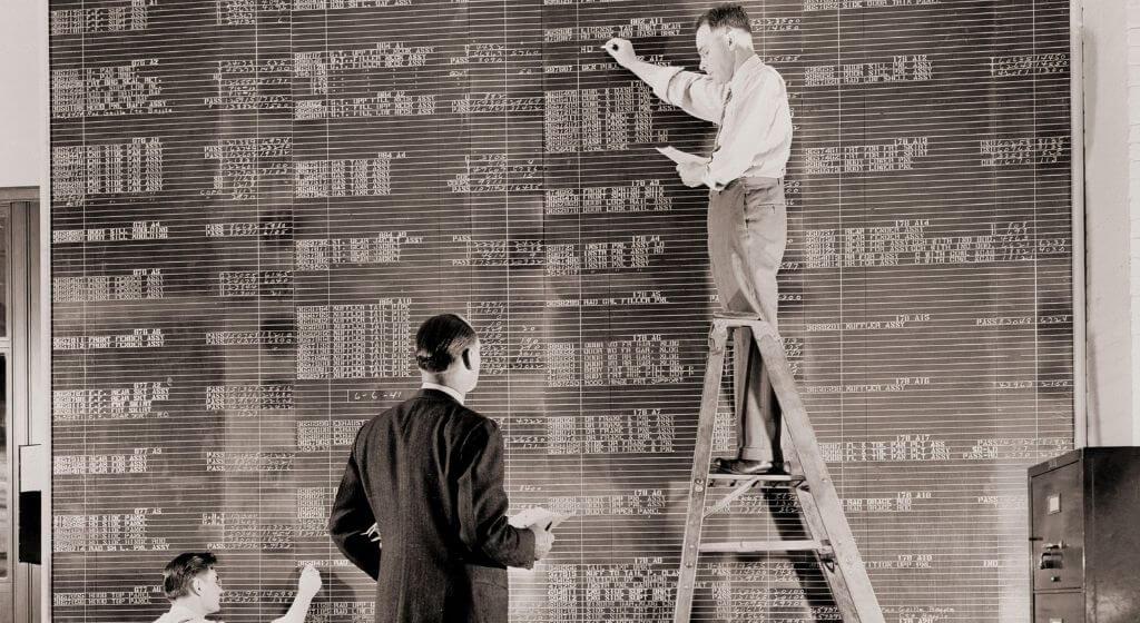 General Motors workers filling out an enormous spreadsheet like chalkboard